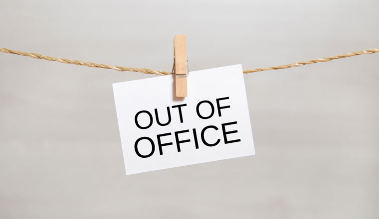 A sign saying out of office is pegged onto a string