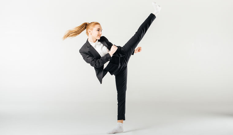 woman high kicking dressed in a suit