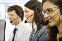 Three young customer service operators sitting in a row and talking on headset. Selective focus on women in middle. Isolated on white background.