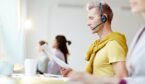 Young businessman working in call centre. He is sitting at the table in headset