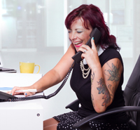 A woman with tattoos on her arm, answers the phone.