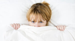 Girl with duvet partly pulled up over her face