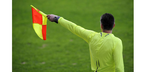 linesman holding up flag for offside