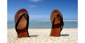pair of flip flops sticking out of the sand