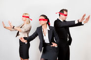 3 business people blindfolded and feeling their way around