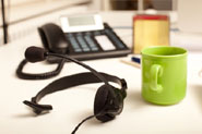 headset and green mug on a desk