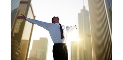 businessman stood in middle of office buildings with arms outstretched