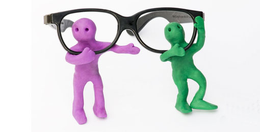 2 coloured men each looking through the lens of a pair of glasses