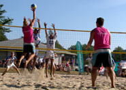 two teams playing beach volley ball