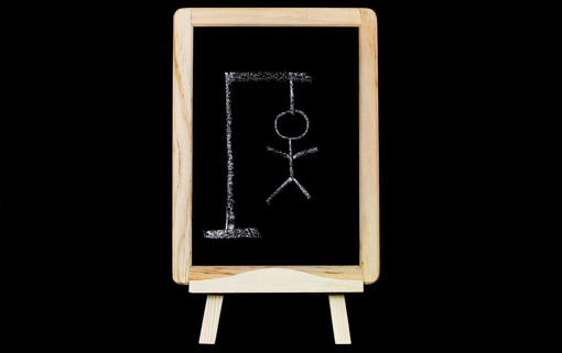 A blackboard has a hangman drawn written in white chalk