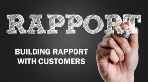 Rapport and building rapport with customers is written in a chalkboard style by a hand