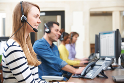A female call centre agent smiles whilst looking away from the camera