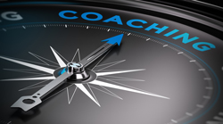 A compass points to the word coaching written in blue