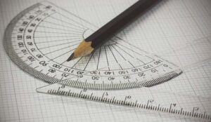 A pencil lies on top of a ruler and a protractor