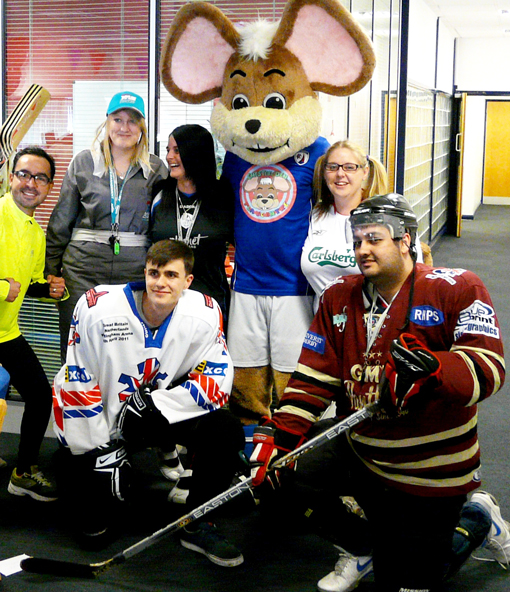 Members of the team pose with a mouse mascot and dress up as hockey players