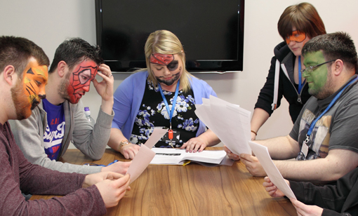 Members of the team with their face painted attend a meeting