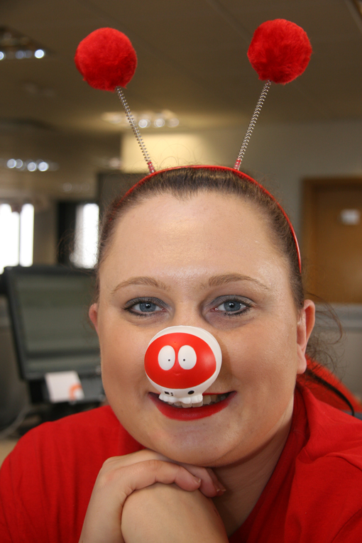 A woman with a red nose and a bobble headband