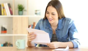 Happy woman reading a letter on a table at home