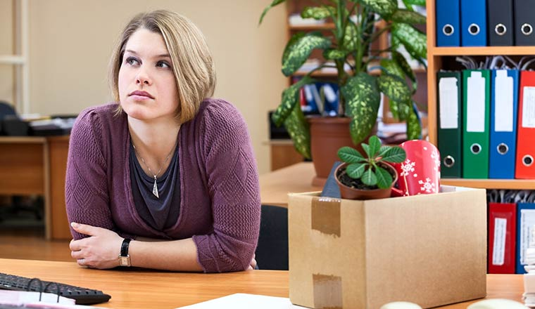 Thoughtful woman sitting in the office with the collected personal things in a box