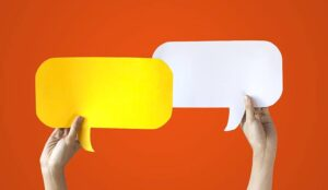 Hands Holding Yellow and White Speech Bubbles Over Orange Background