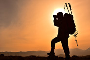 a man with camping equipment looks through binoculars