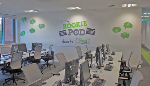 A space filled with desks and computers, with a large poster saying 'The Rookie Pod' on the walls