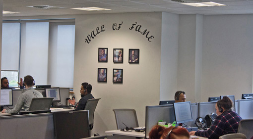 The wall of the contact centre displays a 'wall of fame' where pictures of the advisors who have been recognised are displayed.