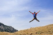 A person jumps into the air on the side of a hill