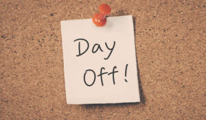 A post it note attached to a cork board saying day off!