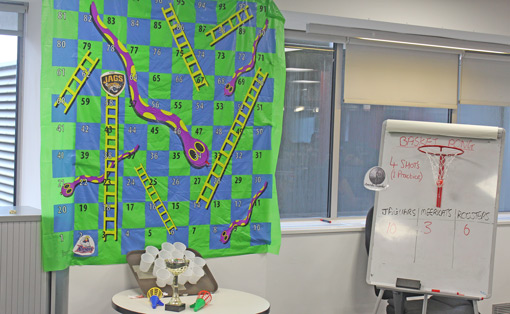 A snakes and ladders board is hung on the wall of a call centre