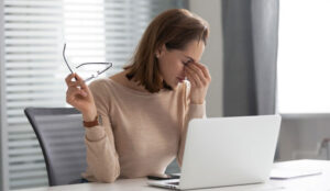 A woman holds her glasses in one hand and the bridge of her nose in the other hand, as if tired from looking at the laptop in front of her