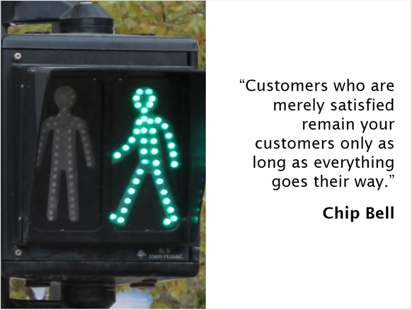 "A crossing sign with the quote from Chip Bell: ""Customers who are merely satisfied remain your customers only as long as everything goes their way""."