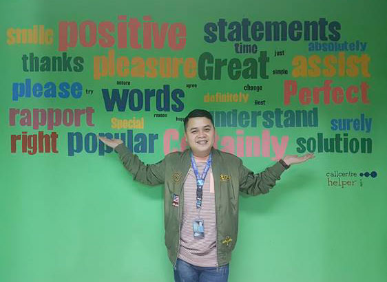 An agent from a contact centre stood in front of a wall of good words, positive statements and positive phrases.