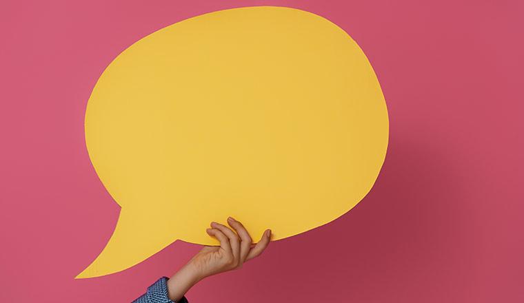 holding yellow speech bubble