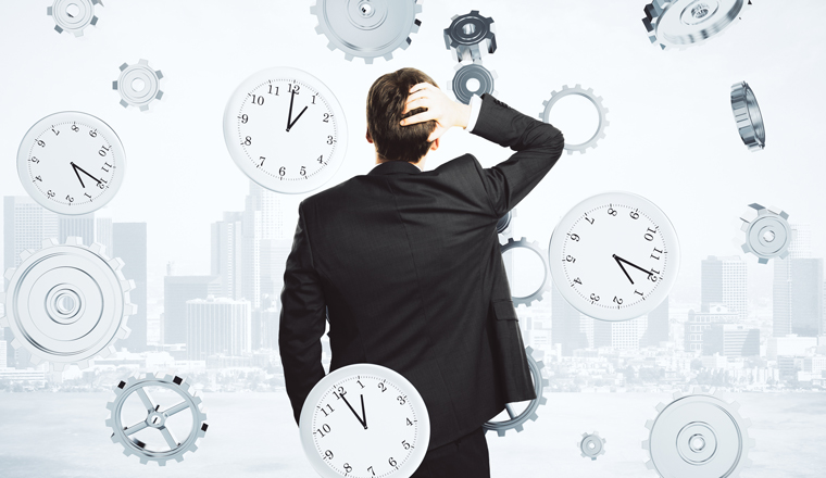 A man holding his head, looking at a cityscape, is surrounded by clocks and cogs falling from the sky