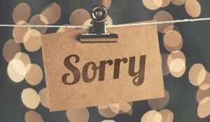 The word sorry is etched onto a piece of wood, clipped to a clothes line