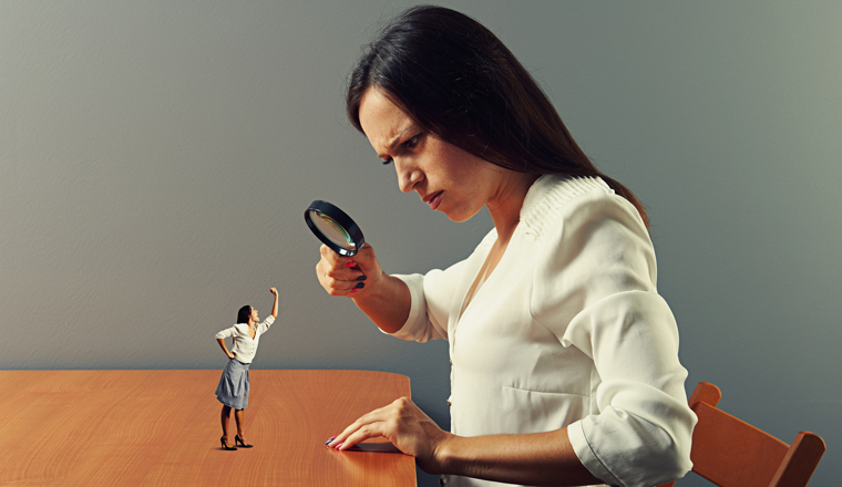 Woman inspecting a smaller version of herself with a magnifying glass