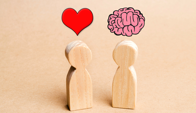 Two wooden dolls, one with a heart above it, the other with a brain