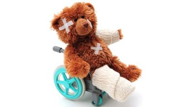 A teddy bear sits in a little wheelchair, with a leg in a bandage and plasters on its head