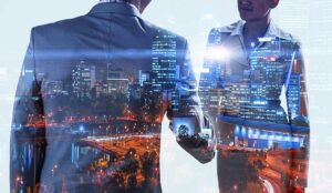Double exposure of business partners shaking hands and modern cityscape