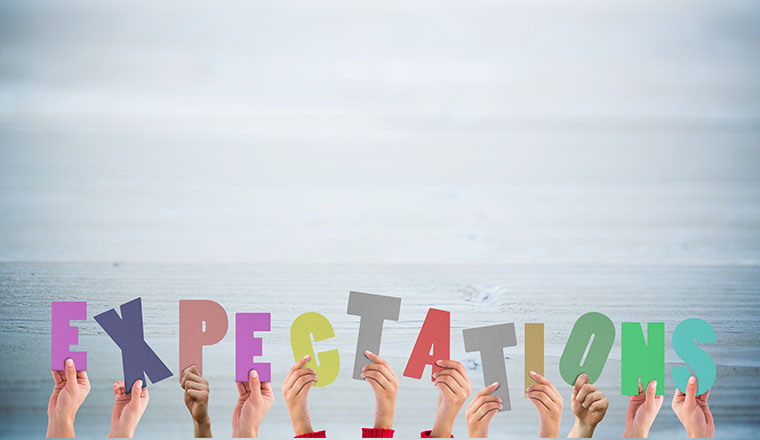 People holding up letters spelling expectations
