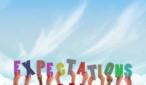 People hold up letters spelling out expectations