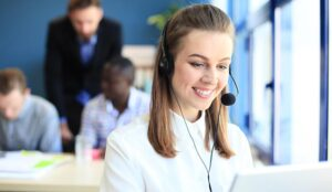 Portrait of call center worker accompanied by her team.