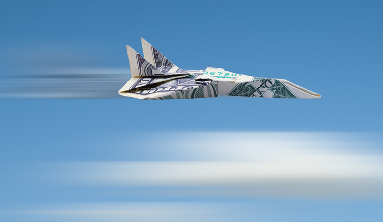 A paper airlplane made of money flys through the sky