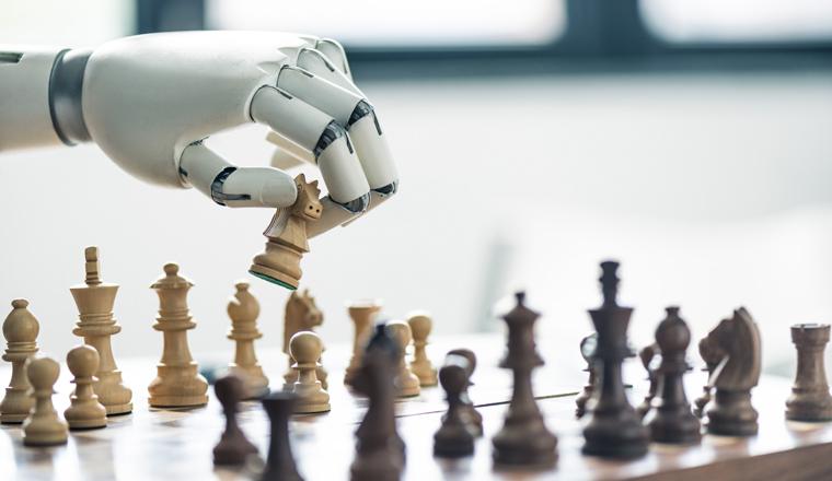 A robot hand plays picks up a white chess piece