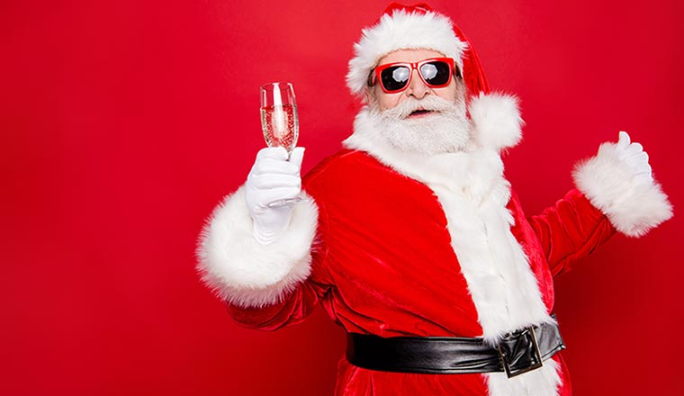 A chilled out santa holds up a glass of wine