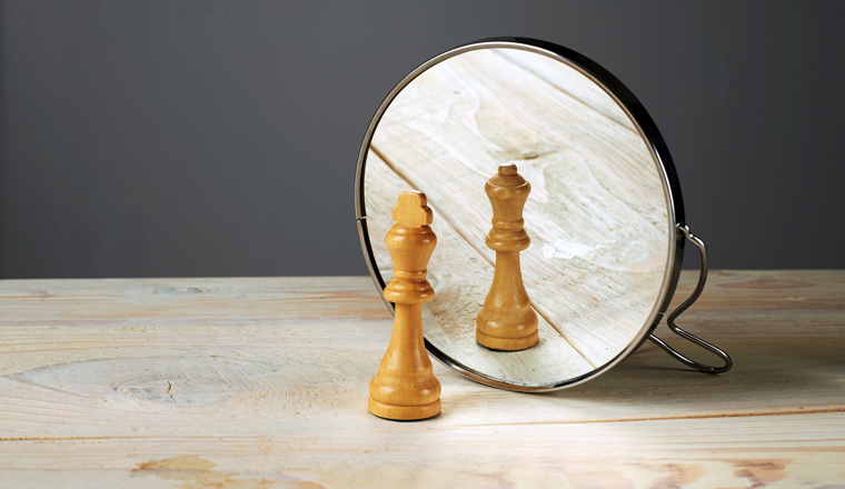 A wooden chess queen piece is reflected by a mirror