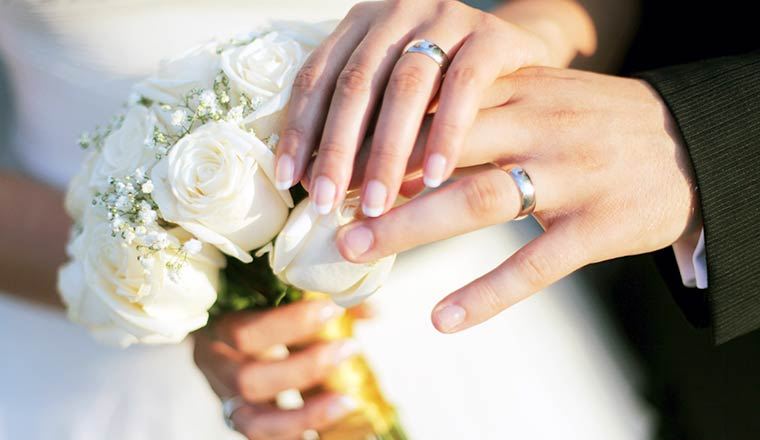 Wedding rings, bouqet and hands holding
