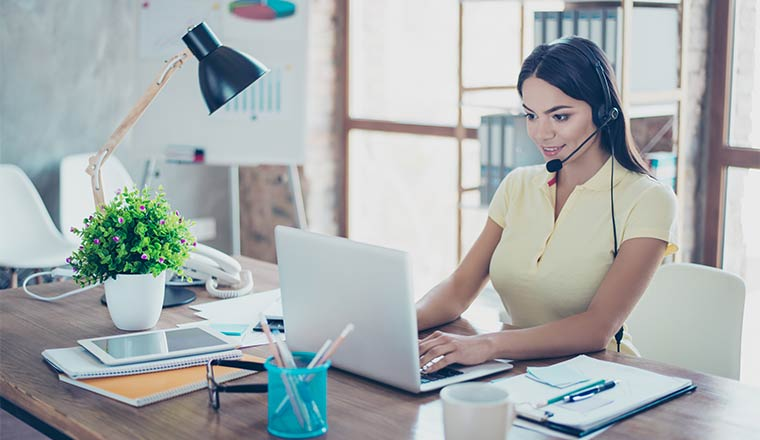 Smiling businesswoman is using headset when talking to customer and typing on her laptop