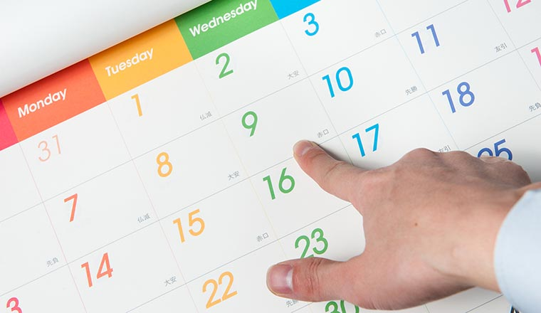 A man points to Wednesday 9th on a calendar